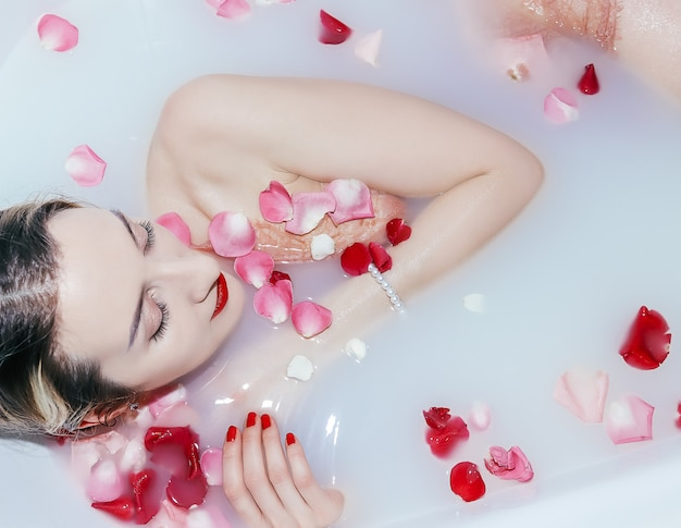 Jeune fille sexy prenant un bain de lait avec des pétales de rose