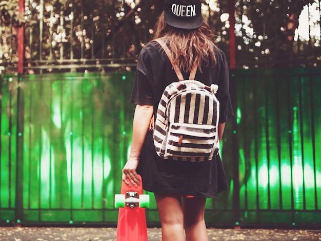 Jeune fille avec shortboard penny orange en plastique derrière le mur vert en casquette