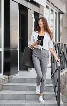 Jeune fille avec la silhouette mince sortant du magasin transportant des sacs en papier.