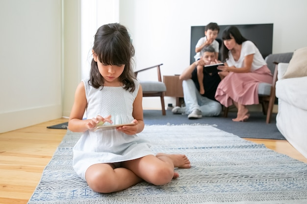 Jeune fille avec smartphone assis sur le sol dans le salon, jouer au jeu pendant que ses parents et son frère à l'aide d'un appareil numérique