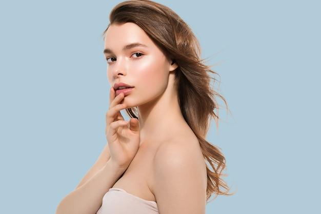 Jeune fille avec soin belle peau propre et saine et main touchant le visage. fond de couleur. bleu