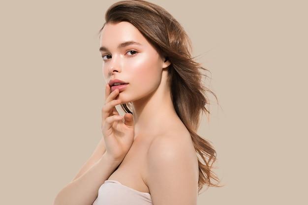 Jeune fille avec soin belle peau propre et saine et main touchant le visage. fond de couleur. brun