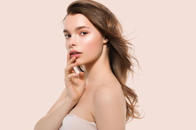 Jeune fille avec soin belle peau propre et saine et main touchant le visage. fond de couleur. rose
