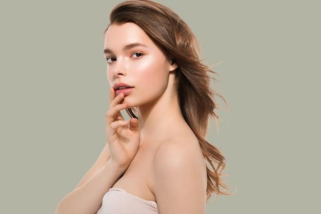 Jeune fille avec soin belle peau propre et saine et main touchant le visage. fond de couleur. vert