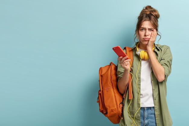 Une jeune fille sombre et perplexe regarde tristement la caméra, ne peut pas comprendre comment utiliser une nouvelle application, n'est pas capable de télécharger une chanson dans une liste de lecture, n'a pas de connexion internet, se tient avec un sac à dos sur un mur bleu