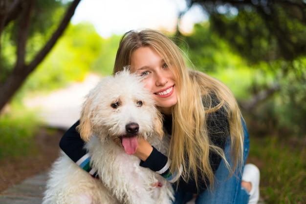 Jeune fille avec son chien dans un parc