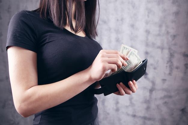 Une jeune fille sort des factures d'un portefeuille