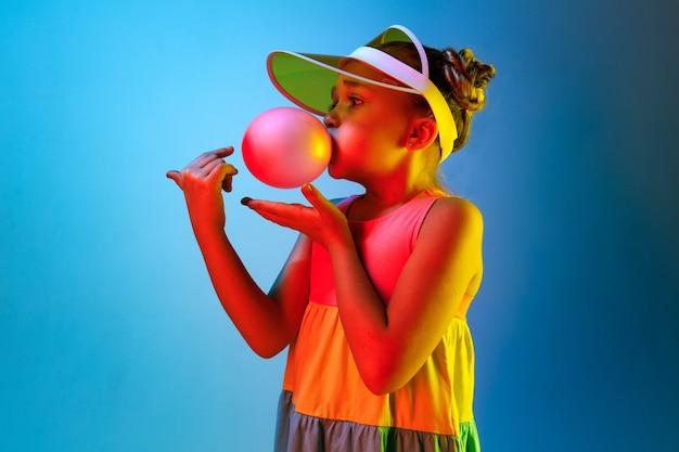 Jeune fille soufflant de la gomme à bulles