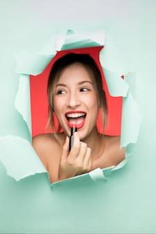 Jeune fille souriante à l'aide de rouge à lèvres