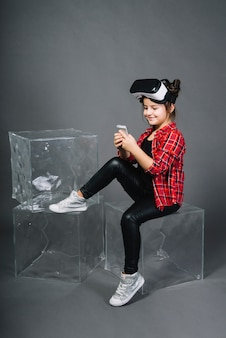 Jeune fille souriante assise sur un bloc à l'aide d'un téléphone portable assis sur fond gris