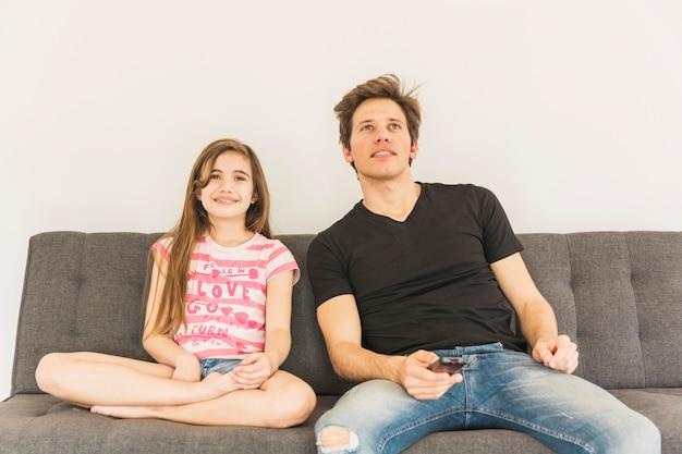 Jeune fille souriante assise sur le canapé avec son père