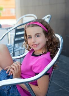 Jeune fille souriante assise sur une chaise en aluminium en plein air
