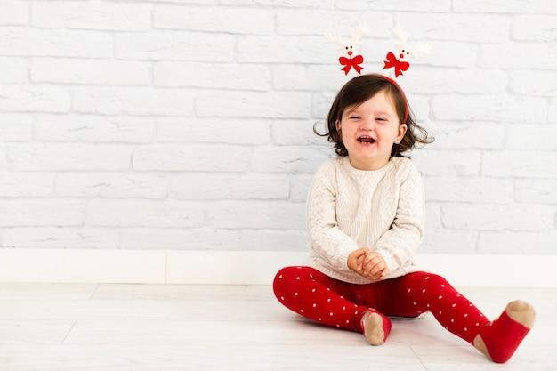 Jeune fille souriante assise à côté d'un mur blanc