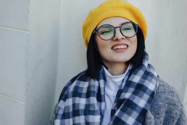 Jeune fille souriante attirante à lunettes en manteau et béret jaune