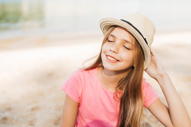 Jeune fille souriante au chapeau en profitant du soleil