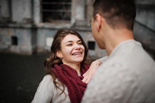 Jeune fille souriante aux bretelles. jeune couple, porter, attaché, chandails chauds, étreindre, amour, vieux, cour, arc, colonnes, ville
