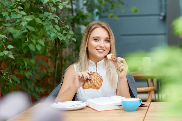 Jeune fille souriante aux cheveux blonds mangeant un croissant, regardant la caméra.
