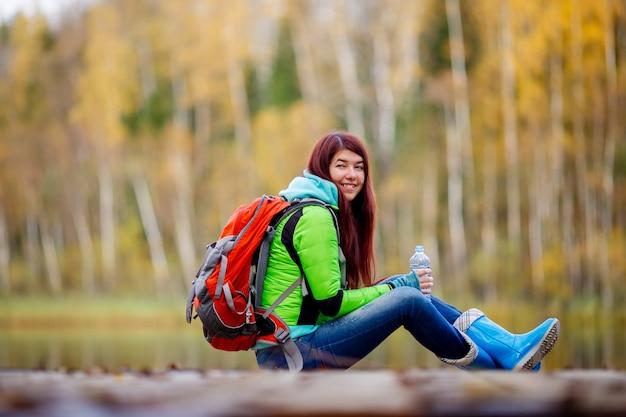 Jeune fille souriante aux cheveux longs assis avec sac à dos sur le pont dans les arbres d'automne