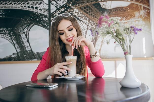 Jeune fille souriante boire un milk-shake au chocolat