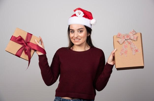 Jeune fille souriante en bonnet de noel montrant des coffrets cadeaux sur fond gris.