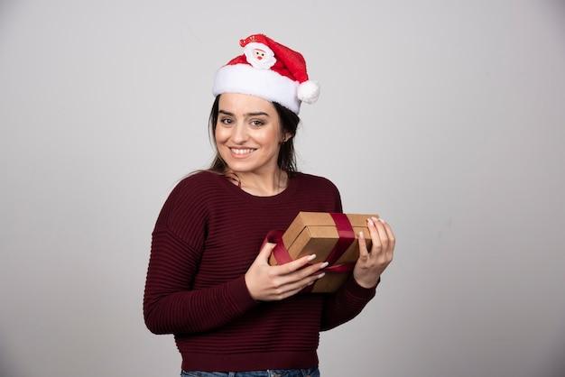 Jeune fille souriante en bonnet de noel tenant une boîte-cadeau avec bonheur.