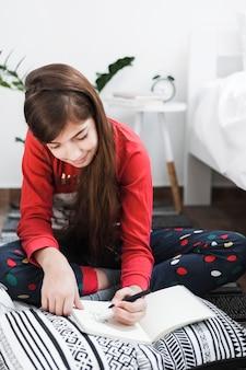 Jeune fille souriante avec des cheveux longs brune dessinant avec crayon sur ordinateur portable