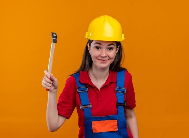 Jeune fille souriante de constructeur tient le marteau et regarde la caméra sur fond orange isolé