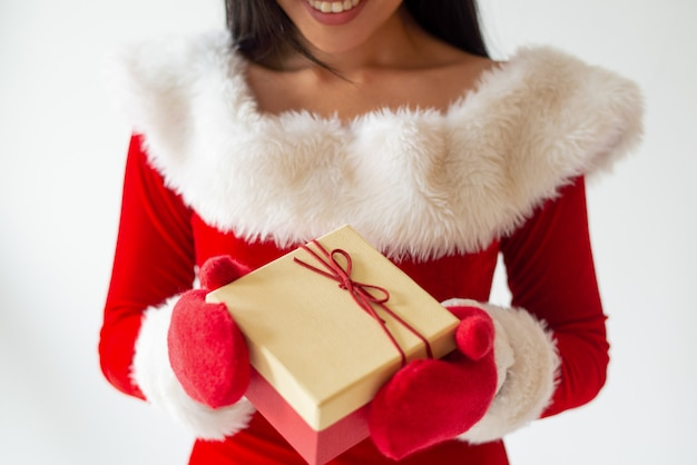 Jeune fille souriante en costume de père noël et mitaines rouges