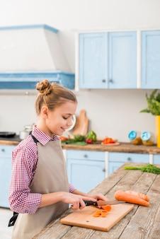 Jeune fille souriante coupe la carotte avec un couteau sur une planche à découper dans la cuisine
