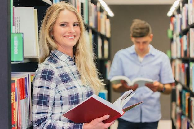 Jeune fille souriante dans la bibliothèque