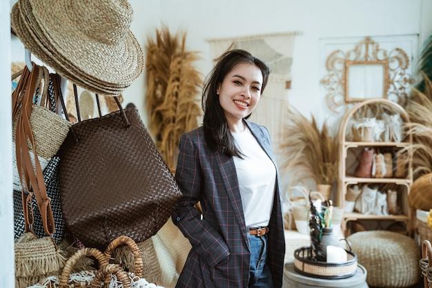 Jeune fille souriante dans le blazer se tiennent parmi les objets d'artisanat dans la boutique d'artisanat