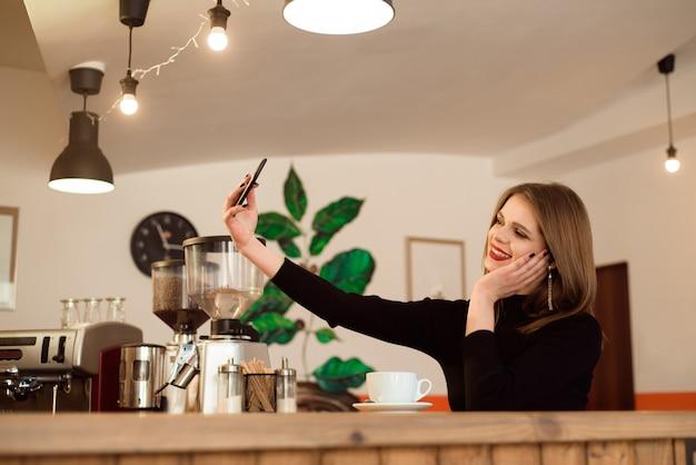 Jeune fille souriante dans un café avec un téléphone.