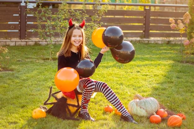 Jeune fille souriante dans un costume d'halloween tenant des ballons oranges et noirs, assise entourée de citrouilles oranges à l'extérieur de l'air avec une grande araignée noire.