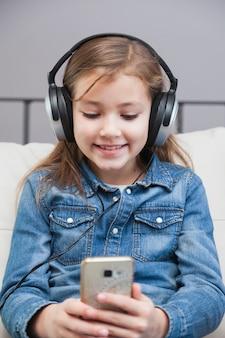 Jeune fille souriante dans les écouteurs, navigation sur smartphone