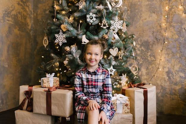 Une jeune fille souriante dans une robe à carreaux se trouve à côté de coffrets cadeaux près d'un arbre de noël