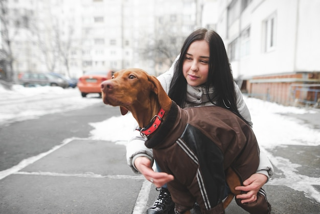 Jeune fille souriante dans des vêtements d'hiver chauds garde un chien habillé o