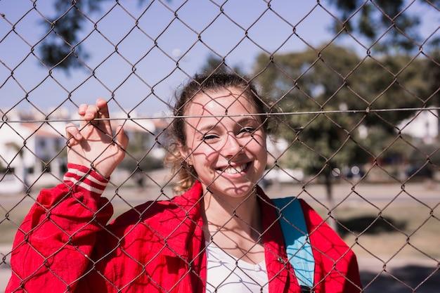 Jeune fille souriante, debout derrière la grille