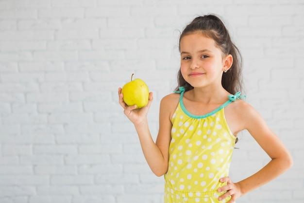 Jeune fille souriante debout devant le mur blanc tenant la pomme verte