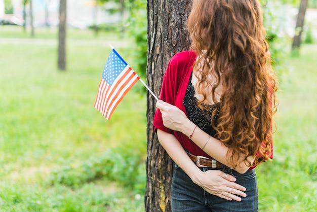 Jeune fille souriante avec un drapeau américain en face de l'arbre