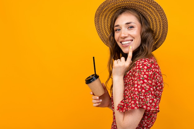Jeune fille souriante avec du café sur fond jaune dans une robe rouge