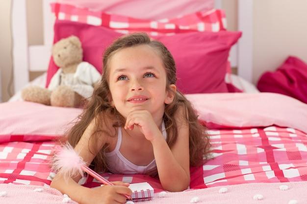 Jeune fille souriante écrivant sur le lit