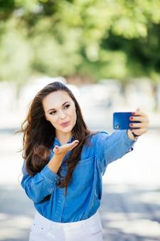 Jeune fille souriante faisant selfie envoyer des bisous sur le fond de la ville