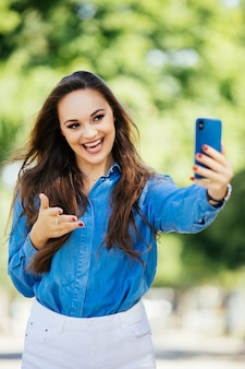 Jeune fille souriante faisant selfie wave sur caméra ou faire un appel vidéo sur le fond de la ville