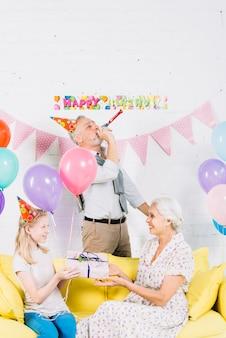 Jeune fille souriante fait un cadeau à sa grand-mère devant l'homme soufflant dans une corne de fête