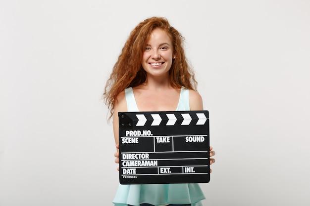 Jeune fille souriante de femme rousse dans des vêtements légers décontractés posant isolé sur fond blanc en studio. concept de mode de vie des gens. maquette de l'espace de copie. tenir un clap classique de fabrication de films noirs.