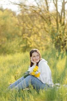 Jeune fille souriante avec des fleurs marchant dans les bois