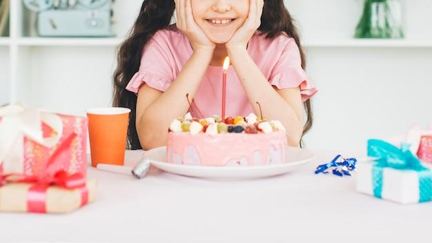 Jeune fille souriante avec un gâteau d'anniversaire