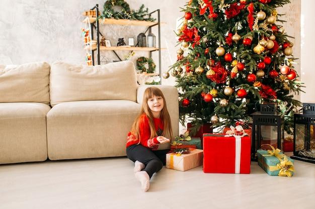 Jeune fille souriante, jouer, près, arbre noël, et, cadeaux