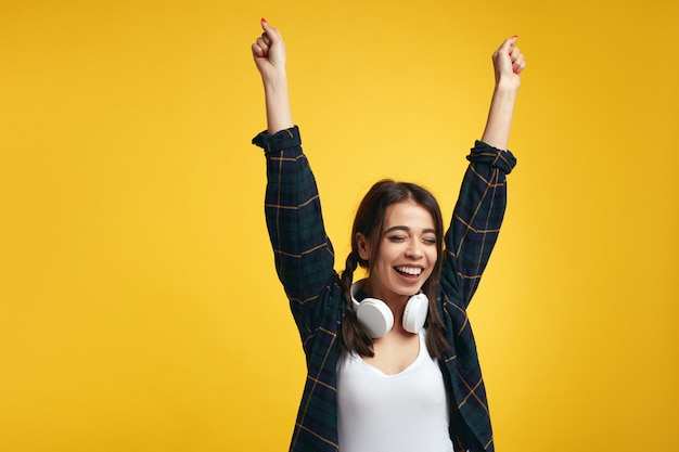 Jeune fille souriante lève les mains en signe de victoire ferme les yeux du plaisir