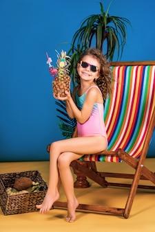 Jeune fille souriante en maillot de bain et lunettes de soleil assis dans une chaise longue arc-en-ciel tenant un cocktail d'ananas avec des pailles colorées et montrant le pouce vers le haut et bronzer
